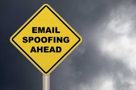 "email spoofing feature image of a yellow caution sign that warns ""email spoofing ahead"""