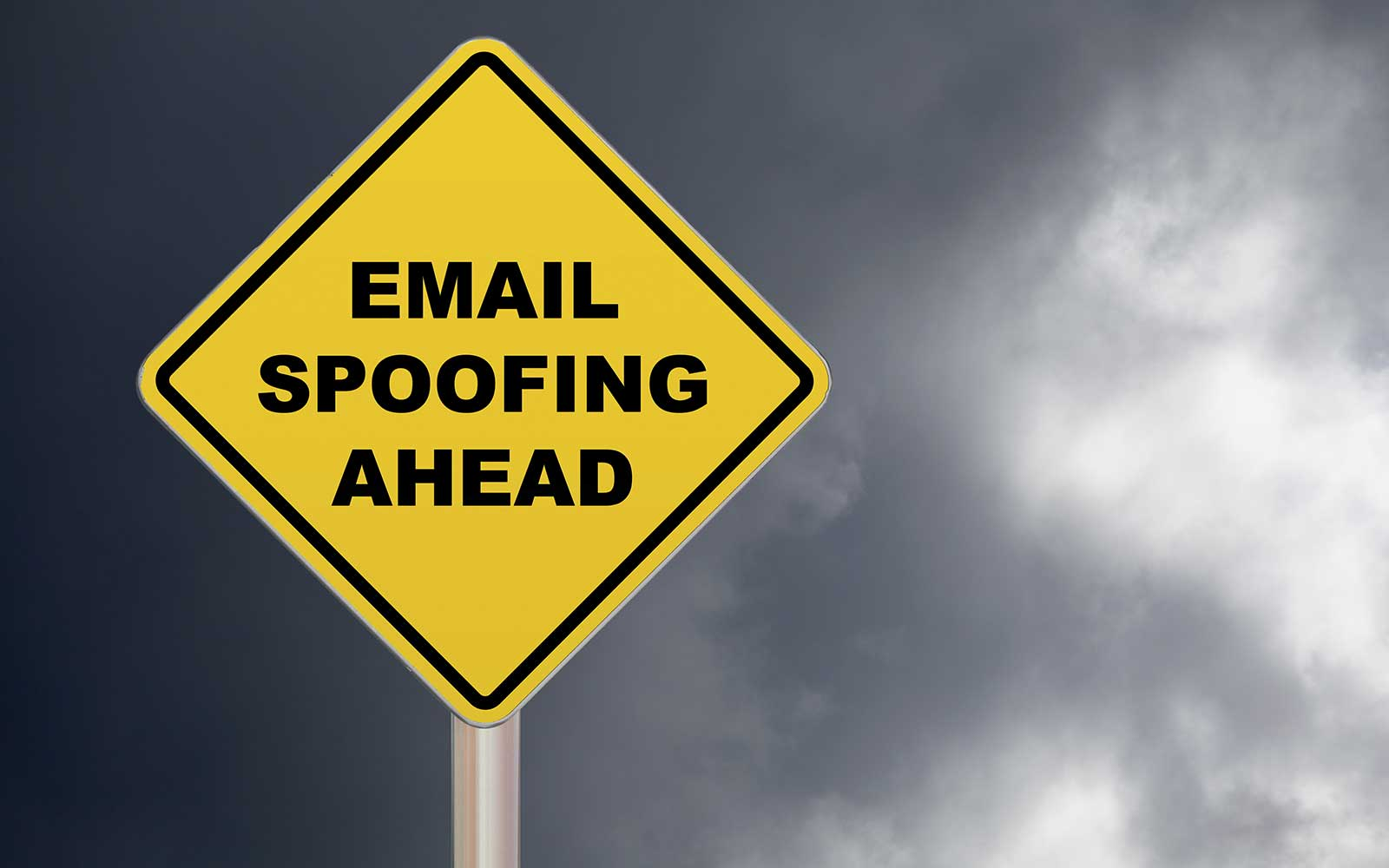 """email spoofing feature image of a yellow caution sign that warns """"email spoofing ahead"""""""